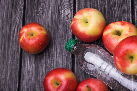 sealed: Beautiful fresh organic red yellow apples around sealed full bottle of tonic on grey wooden table, horizontal photo Stock Photo
