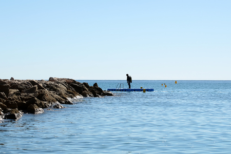 skindiver: Photo long shot of one skin-diver in diving suit standing on float board near stone pier in calm blue sea silhouetted against clear sky day time summer on seascape background, horizontal picture Stock Photo