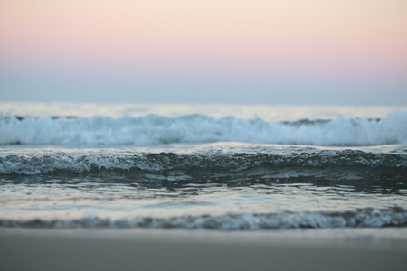 murky: Photo closeup of beautiful clear blue sea ocean water waves hit seashore wet beige sand with splashes spindrifts spoondrifts in rosy murky evening over seascape background, horizontal picture