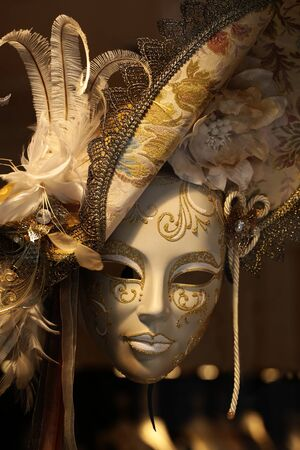 distinctive: Photo closeup of one distinctive ornate Venetian carnival white and golden mask woman face with beautiful decoration in hat with natural feather classic accessory on blurred background, vertical picture