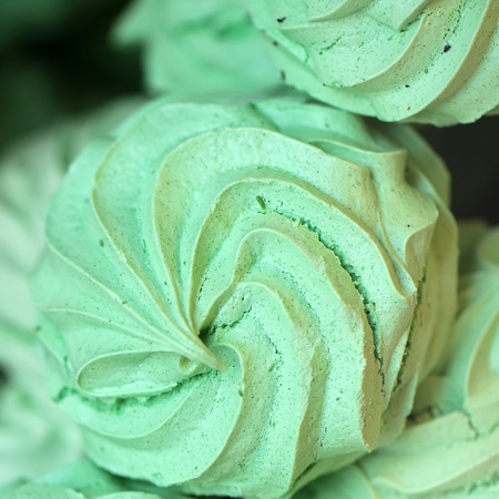 Photo closeup of green marsh-mallow souffle sweetmeat mass sweet delicacy confectionery cake pastry on blurred background, square picture Stock fotó
