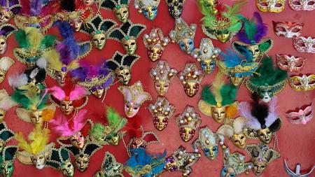 mascaras de carnaval: Foto de muchas m�scaras venecianas de carnaval distintivos de varios colores con adorno de plumas naturales pantalla cl�sica entre los accesorios para la venta al aire libre en la pared en el fondo rojo, imagen horizontal Foto de archivo