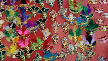 distinctive: Photo of many distinctive Venetian carnival masks of various colors with beautiful decoration natural feather classic accessory display for sale outdoor on wall on red background, horizontal picture