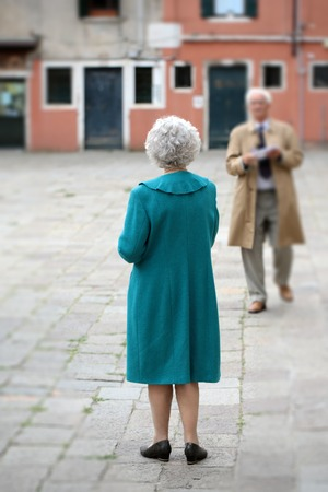 town square: Photo closeup of silver-haired senior couple woman in turquoise coat back view and blurred well-dressed aged man in old town square on cityscape background, vertical picture