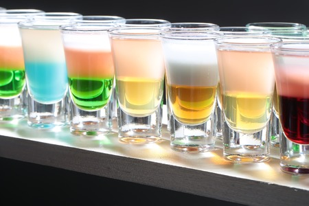 shooter drink: Variety of colorful green blue yellow red and white beautiful alcohol sweet shooters shots cocktail fresh beverage in small glasses standing in row on bar studio closeup, horizontal picture