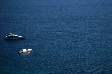 blue vessels: Photo of beautiful white modern yachts boats vessels offshore in calm blue sea day time silhouetted against seascape background, horizontal picture