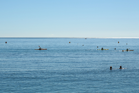 plan éloigné: Photo long shot of people swimming and rowing canoe paddling in calm blue sea silhouetted against clear sky day time on seascape background, horizontal picture
