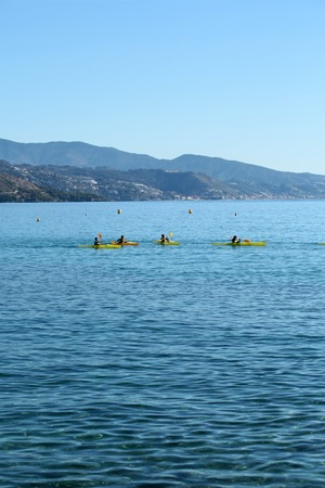plan éloigné: Photo long shot of group of people rowing yellow canoes paddling in beautiful clear calm blue sea with ripples pebble seabed seaside mountains summer day on seascape background, vertical picture