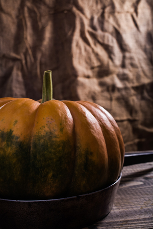 segmented: One raw flat round orange squash with smooth segmented surface green blotch and stem on pan with black handle on wooden table on burlap background, vertical picture