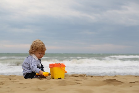 murky: Cute fair-haired blond kid tiny little child baby boy sitting on sand and playing with yellow toy trowel bucket on beach on windy murky day on blurred seascape background, horizontal picture Stock Photo