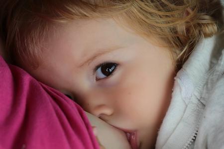 Baby fair-haired blond hazel-eyed given breast milk breastfeeding cute portrait on motherhood background, horizontal picture Stock Photo