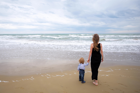 wet jeans: Mother in black dress and son in shirt jeans back view standing on sea shore beach wet sand watching waves running on coast on windy murky day on seascape background, horizontal picture
