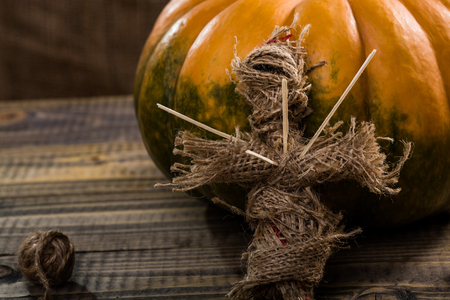 cross linked: Halloween concept of sackcloth voodoo doll pierced with sticks on chest with clew of twine near round orange pumpkin with green spots on wooden table, horizontal photo Stock Photo