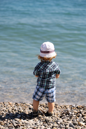 pebble beach: Baby boy cute fair-haired blond kid tiny little child wearing checked shirt shorts and white hat standing on pebble beach on sunny day back view on beautiful seascape background, vertical picture Stock Photo