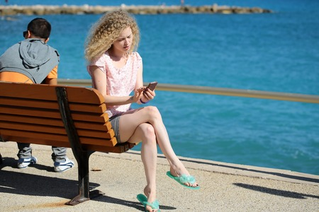 long hair man: Woman young attractive with long curly blond hair playing with smart phone sharing wooden bench with male on promenade along blue sea shore on sunny day on seascape background, horizontal picture