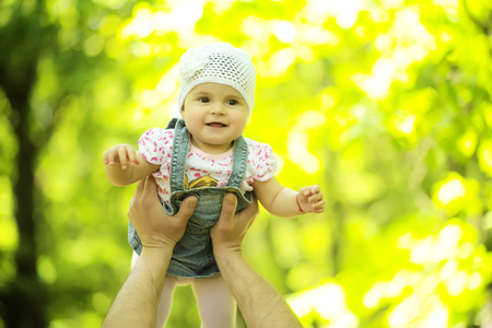 air baby: Baby girl smiling hazel-eyed kid tiny little child wearing white flower beanie hat lifted in air high by hands portrait outdoor on summer day on blurred sunny background, horizontal picture