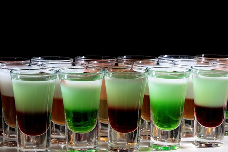 shooters: Closeup of set of many bright green red and white tasty strong alcohol shooters shots cocktail drinks in beautiful glasses menu for merry night party in club on black background, horizontal picture Stock Photo
