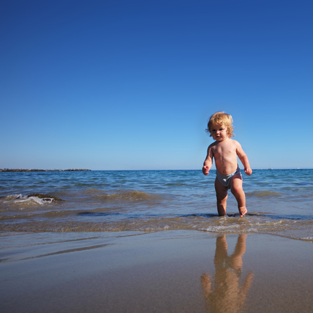 fair haired: Baby boy one cute fair-haired blond kid tiny little child walking on sea reflection in water waves wet sand sunbathing on warm sunny summer day bright blue sky on seascape background, square picture