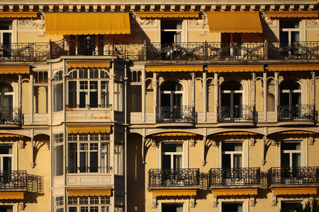 awnings windows: MONTREUX, SWITZERLAND - September 18, 2015: Beautiful ornate yellow building facade of Montreux Palace Hotel with balconies and sun awnings over windows, horizontal photo Editorial