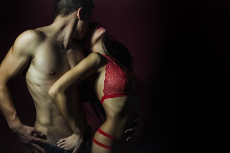 Pretty young couple of undressed sensual woman with beautiful straight body in red lace erotic lingerie with muscular man posing indoor on dark purple background, horizontal picture Stock Photo