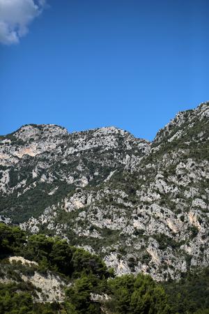 plan éloigné: Photo long shot de grands arbres à feuilles persistantes sur de belles têtes sommets des montagnes avec des falaises élévation naturelle de la surface de la terre nuage blanc sur le ciel bleu clair sur fond de paysage, image verticale Éditoriale