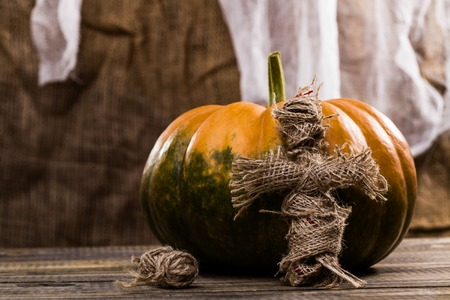 cross linked: Halloween orange and green pumpkin with magical handmade burlap voodoo doll with balls of twine on wooden table on white and brown cloth background, horizontal photo Stock Photo