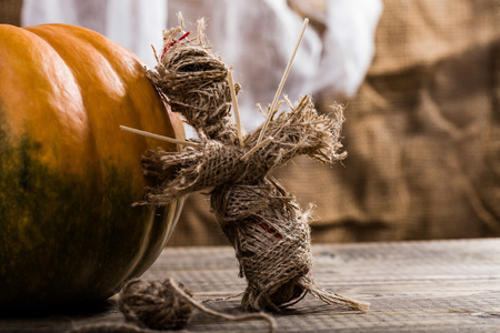 Closeup photo of terrible Halloween burlap voodoo puppet pierced with sticks on chest standing near orange pumpkin with clew of cord on table on white air fabric background, horizontal picture Imagens