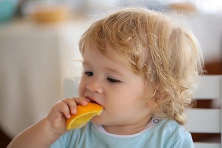 Nette blonde blond Hasel Augen Kind kleines Kind Baby essen orange Frucht Foto Porträt auf unscharfen Hintergrund, horizontal Bild Standard-Bild