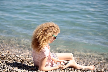 pebble beach: Woman one young with blond curly hair wearing sun glasses and playing with smart phone reclining on pebble beach on blue sea shore sunny summer day on blurred seascape background, horizontal picture