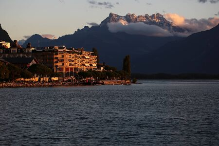 montreux: MONTREUX, SWITZERLAND - September 18, 2015: Beautiful autumn landscape of Lake Geneva with hotels on embankment of Montreux on mountains covered with clouds background at sunset, horizontal photo