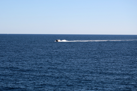 day time: Photo of modern motor boat speed vessel offshore in calm blue sea silhouetted against clear sky day time on seascape background, horizontal picture