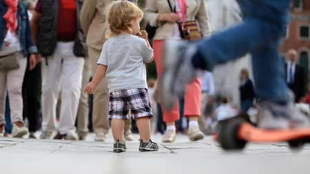 flagstone: Photo back view of cute fair-haired blond kid tiny little child baby boy eating bun standing on flag-stone pavement in crowd cityscape on blurred grey background, horizontal picture