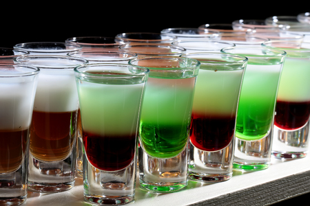 shooters: Row of many colorful vivid green red orange colored alcohol tasty cocktail shooters drinks in drinking glasses standing on white bar on black background closeup studio, horizontal picture