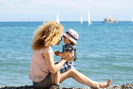 pebble beach: Mother young woman with son sitting on her knees on pebble beach blue sea shore enjoying beautiful sunny summer day together on blurred seascape background, horizontal picture