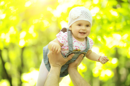 lifted hands: Baby girl smiling hazel-eyed kid tiny little child wearing white flower beanie hat lifted in air high by hands portrait outdoor on summer day on blurred sunny background, horizontal picture