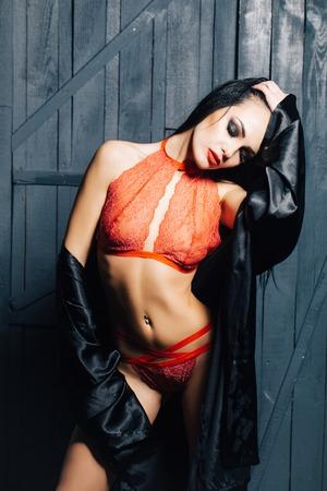 femme se deshabille: Attractive jeune femme brune d�v�tue avec un beau corps droit en dentelle rouge lingerie �rotique et soie robe de nuit noire posant int�rieure sur fond de bois, l'image verticale