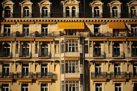 awnings: MONTREUX, SWITZERLAND - September 18, 2015: Old building facade of Montreux Palace Hotel with rows of balconies and sun awnings over windows, horizontal photo