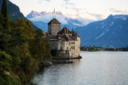convict lake: MONTREUX, SWITZERLAND - September 18, 2015: Pecturesque view of ancient Chillon castle on shores of Lake Geneva in canton of Vaud on Alps mountains covered with clouds background, horizontal photo Editorial