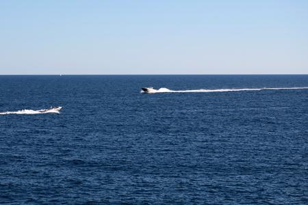 cielo y mar: Foto de vasos de velocidad lanchas a motor modernos en alta mar en el mar azul en calma silueteado contra el tiempo Cielo despejado en el fondo marino, cuadro horizontal