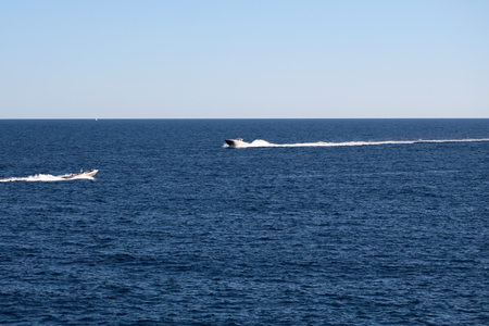 sea in the horizon: Photo of modern motor boats speed vessels offshore in calm blue sea silhouetted against clear sky day time on seascape background, horizontal picture Stock Photo