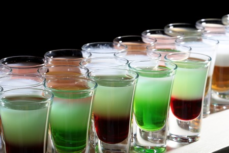 shooters: Many colorful green red white delicious sweet shooters cocktail alcoholic liquid in beautiful drinking glasses standing in line on bar night club party on black background closeup indoor, horizontal