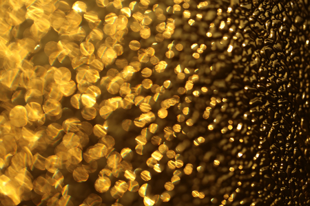 prominence: Yellow golden beautiful abstract gleam glass surface with shiny sparkling pretty golden color texture backdrop closeup, horizontal picture