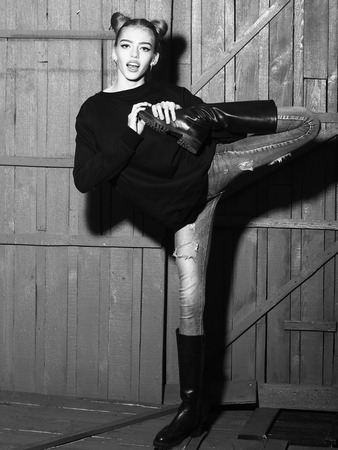 torn jeans: One straight slender funny young woman with cool hairstyle in torn jeans and black sweater with flexible body standing in studio on wooden backdrop black and white, vertical picture