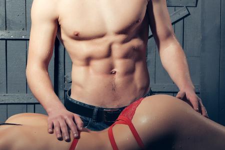 nackter junge: Sexy junge entkleideten sinnliche Frau mit dem schönen geraden Körper in rot erotische Spitze Unterwäsche in der Nähe von muskulösen Mann berühren Gesäß liegend Innen posiert auf hölzernen Hintergrund, horizontale Bild