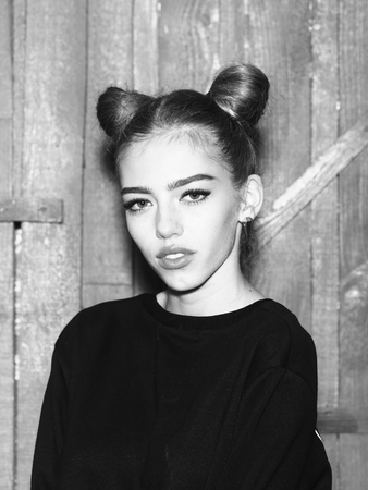 black sweater: Portrait of one funny young thoughtful woman with cool hairstyle in black sweater with flexible body standing in studio on wooden backdrop black and white, vertical picture