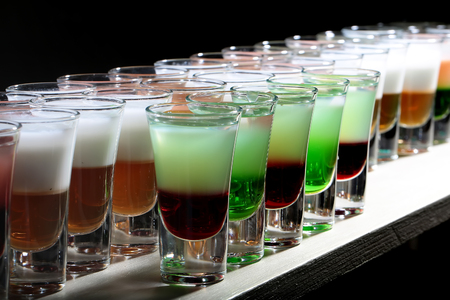 shooters: Group of fresh cold colorful yummy cocktail shooters strong drinks in beautiful drinking transparent glasses standing in row on white bar studio closeup on black background, horizontal picture