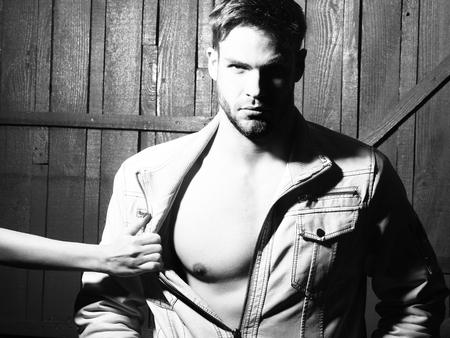 nackte brust: Sexy junge stilvolle sch�nen muskul�sen Macho Mann mit Bart in der Jacke mit nackten Brust und weibliche Geliebte Hand Auskleiden ihn auf h�lzernen Hintergrund schwarz und wei�, horizontale Foto im Studio Innen stehen