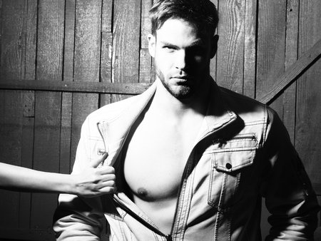 and the horizontal man: Sexy young stylish handsome muscular macho man with beard in jacket with bare chest and female mistress hand undressing him standing indoor in studio on wooden backdrop black and white, horizontal photo Stock Photo