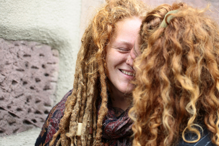 redheaded: COLMAR, FRANCE - September 18, 2015:  Redheaded curly man kisses smiling woman with dreadlocks on street in Colmar city, horizontal photo