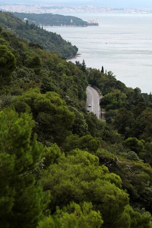 splendid: Italy - Month 09.2015: Splendid sight of italian serpentine asphalt road on hill between beautiful green tree foliage and coast of mediterranean sea and blue sky outdoor, vertical picture